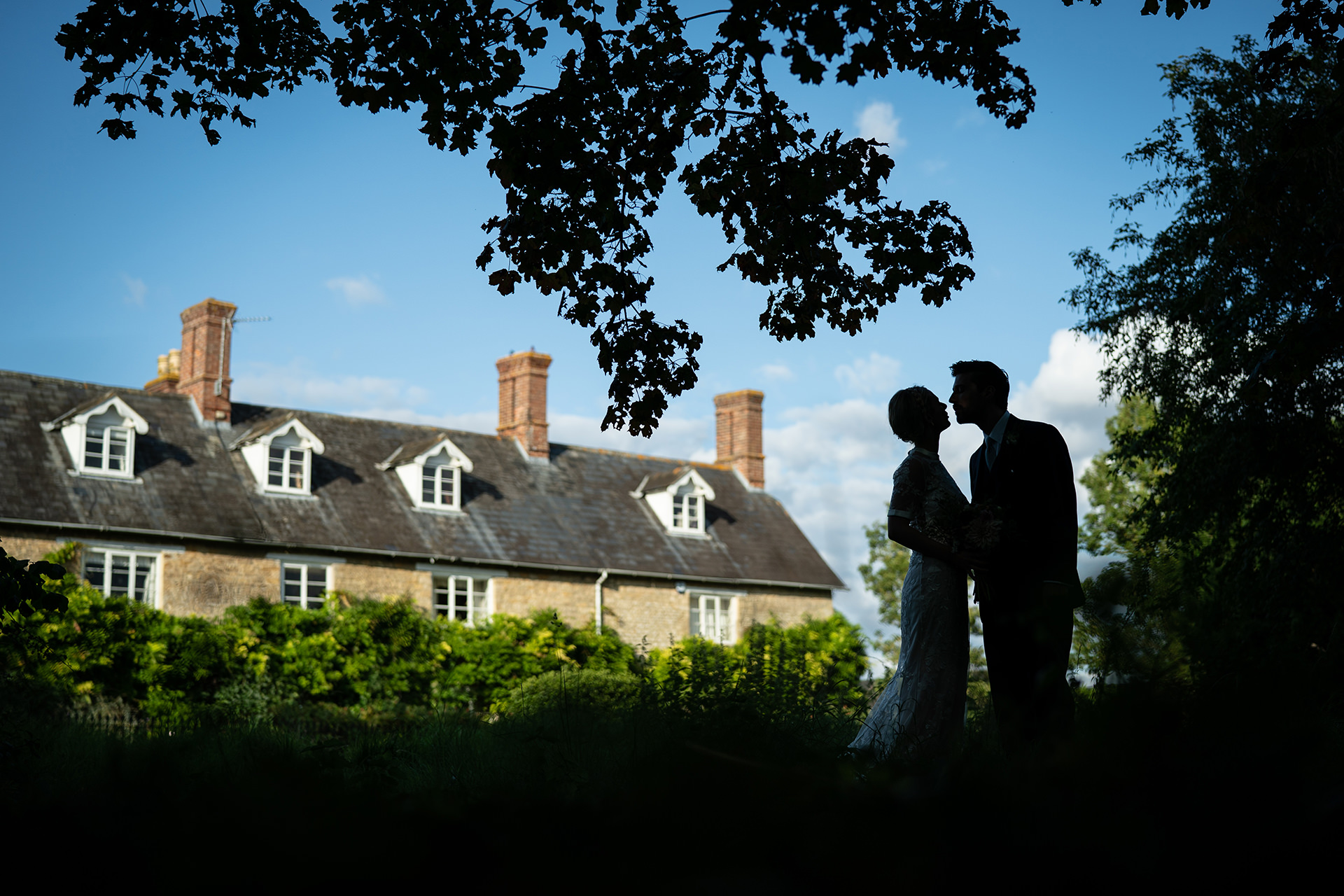 Natural wedding portrait of Newlyweds in front of Farmhouse