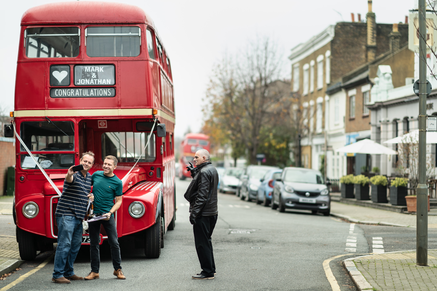 Two Grooms take a selfie with a London Routemaster Bus