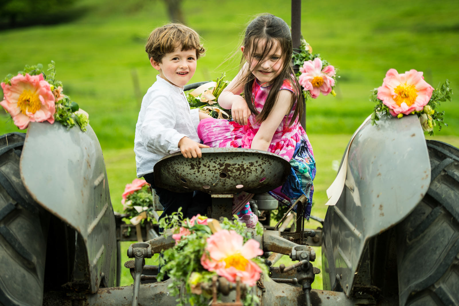 Children play on a tractor with wedding decorations