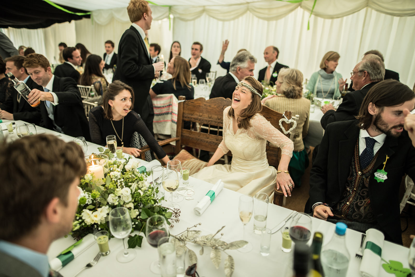 Bride sits at table in marquee