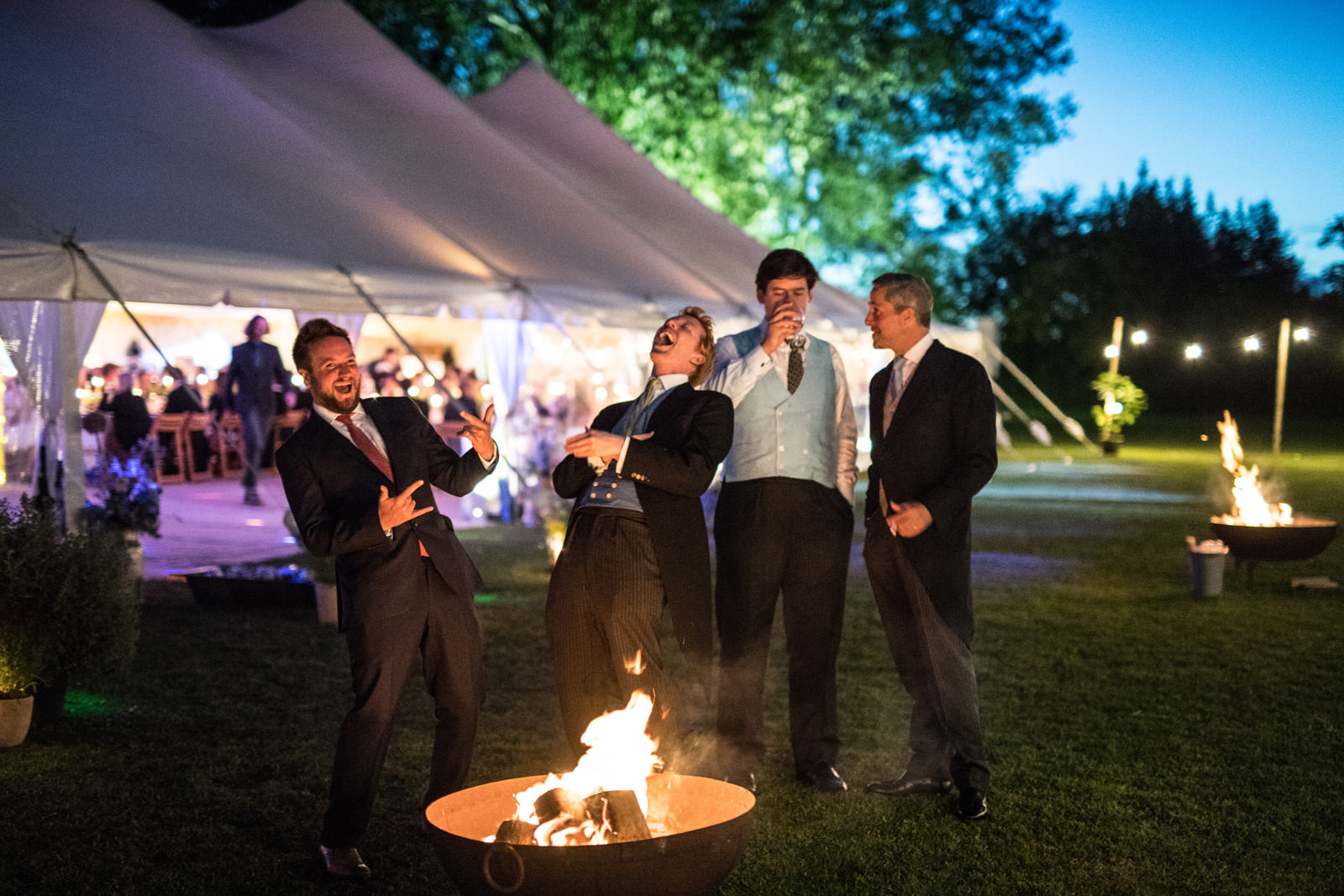 Wedding guests laughing by a fire pit