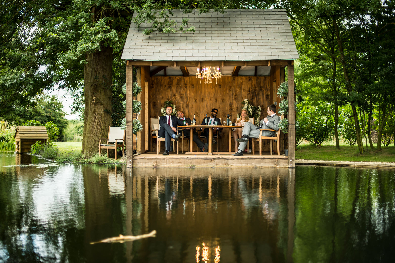 Wedding guests site undercover in a lakeside feature