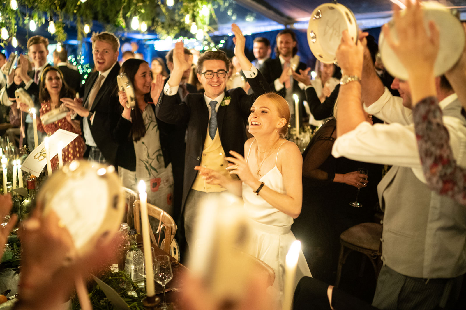 Couple greeted with tambourines at their marquee table for their wedding meal