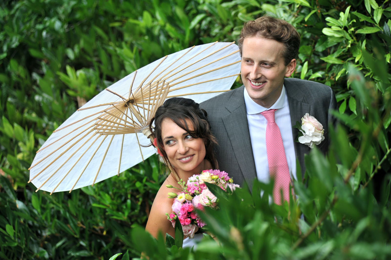 Wedding newlyweds with parasol among the laurels at the Larmer tree