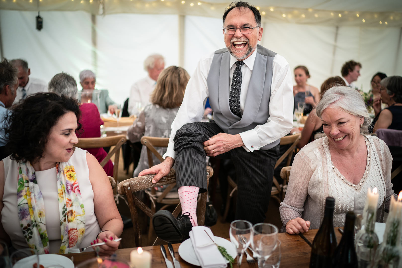 Father of the Bride shows off his socks in a Dorset Marquee
