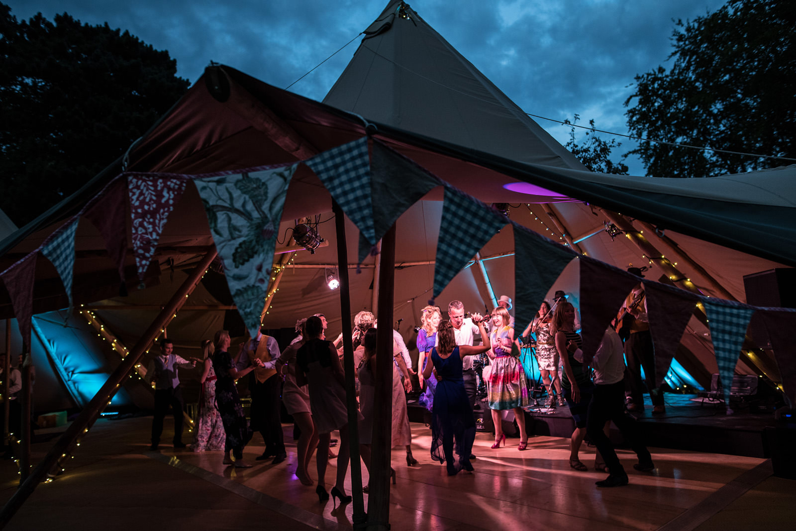 Guests dance in a Tipi Marquee with bunting
