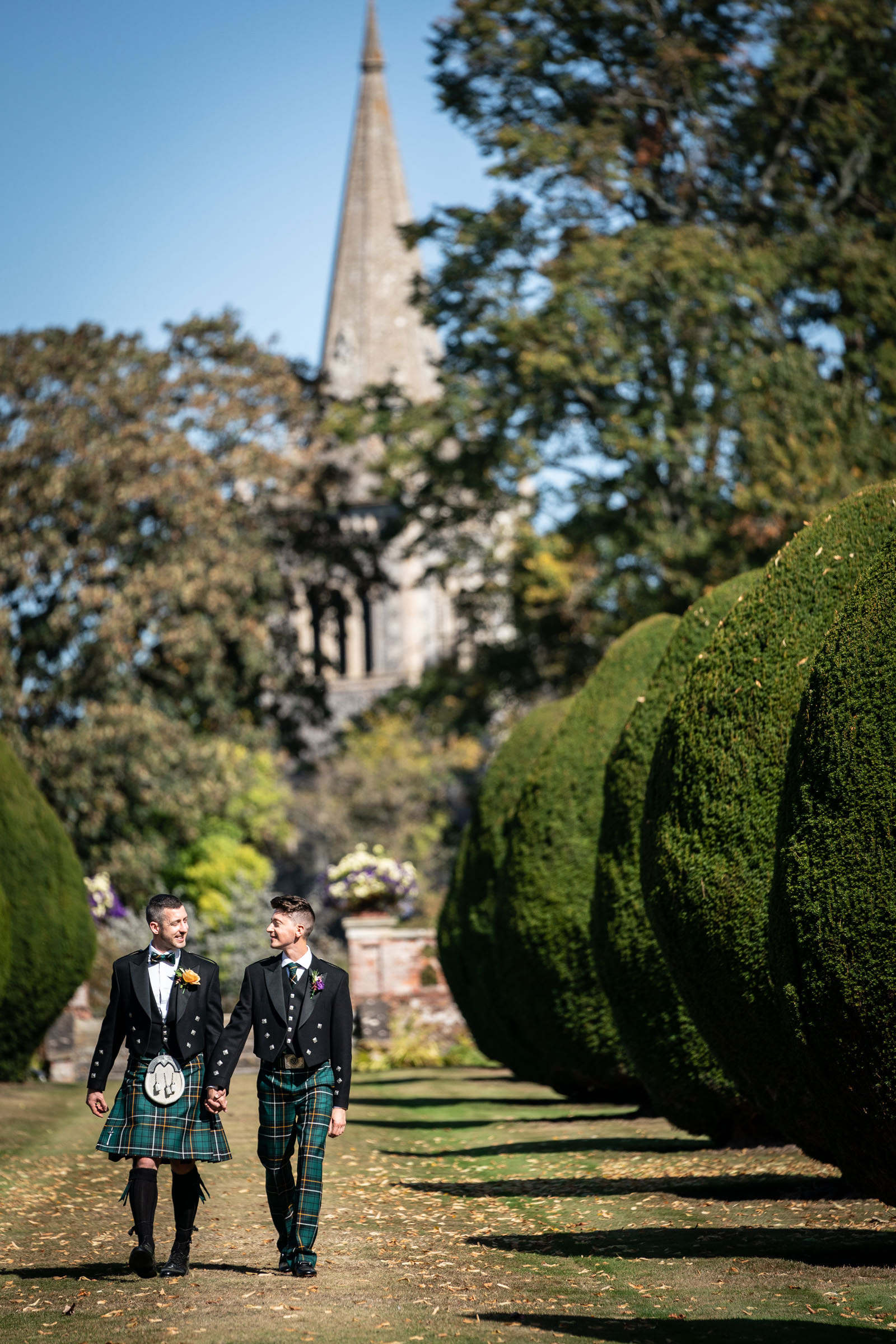Two Grooms walk down the Irish Yew trees at The Elvetham