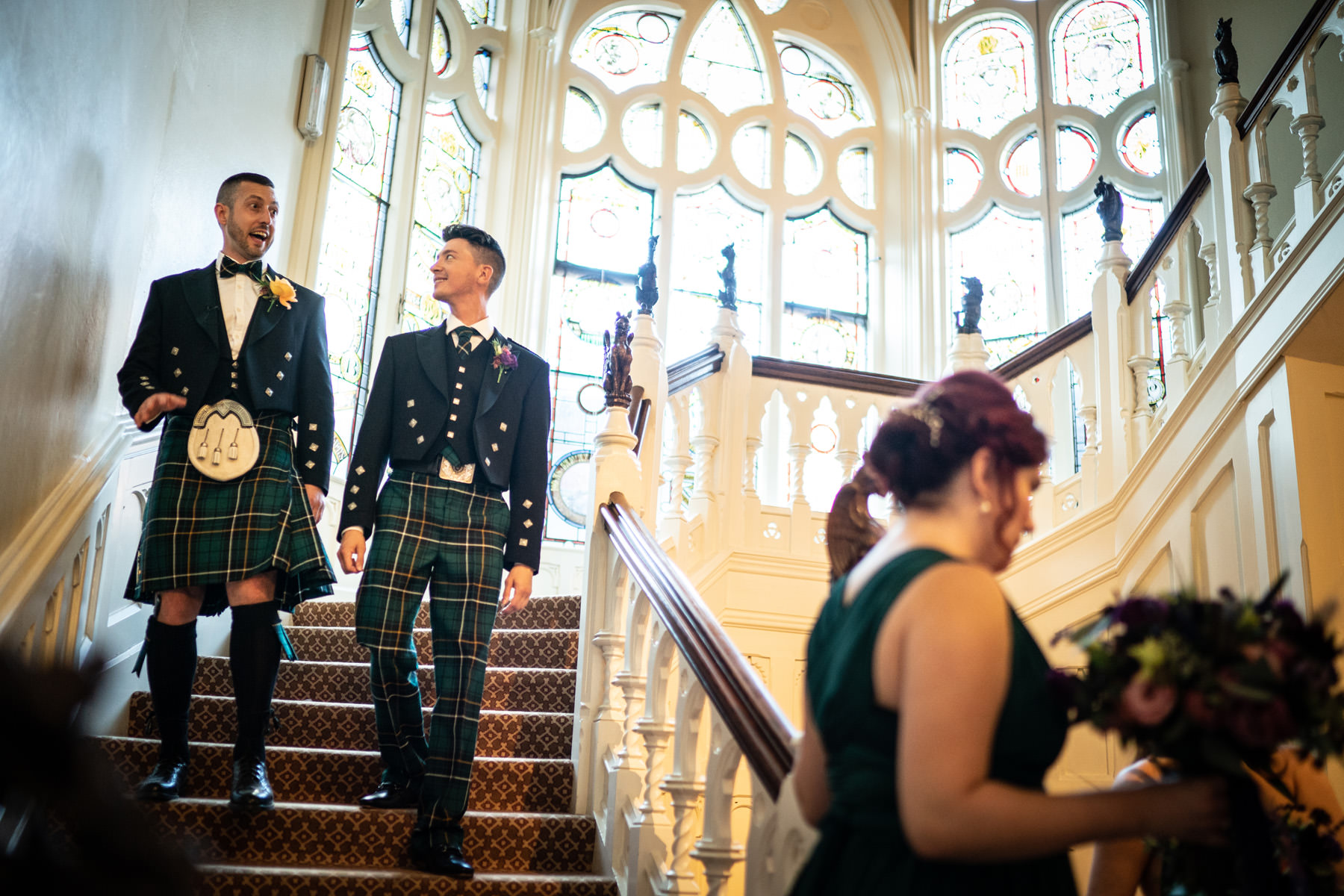 Two Grooms in Kilts descend the spiral stairs at The Elvetham Hotel