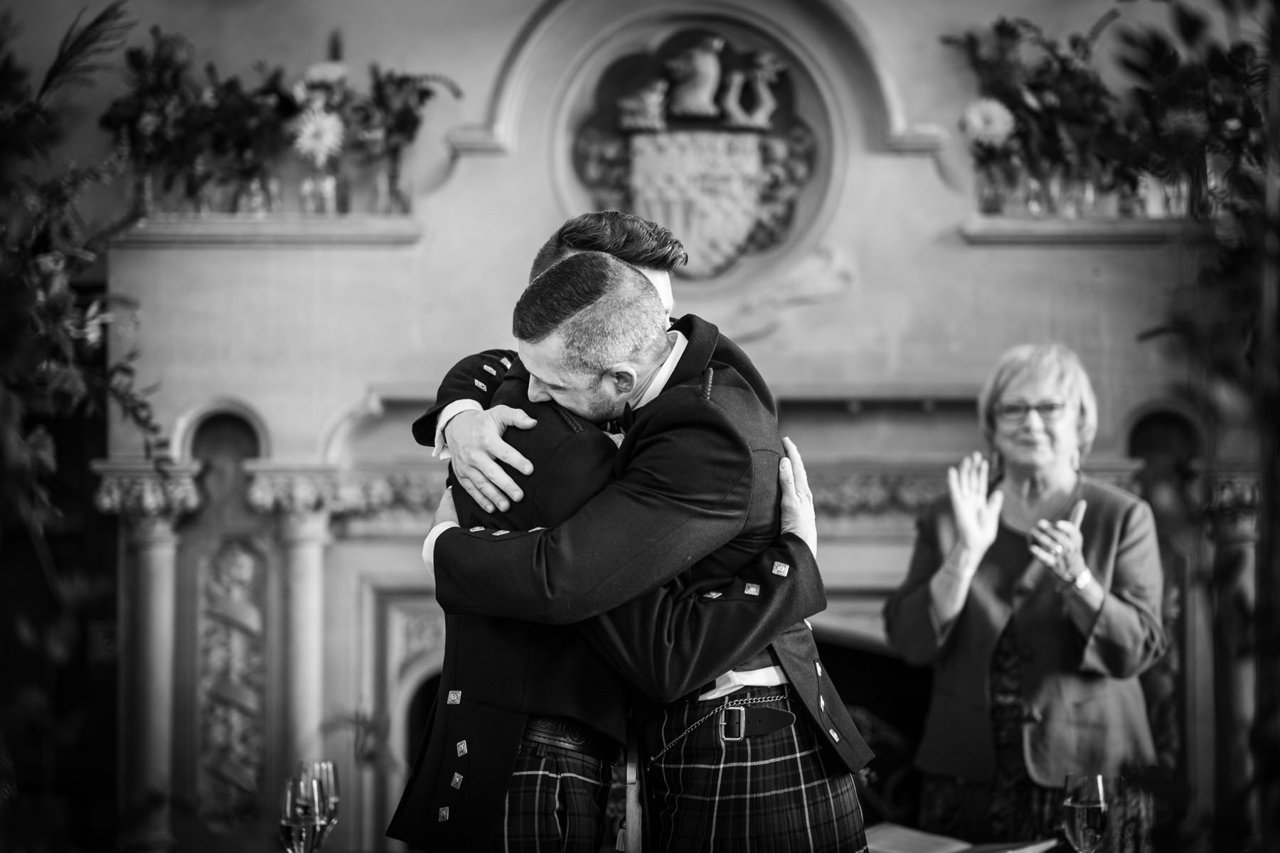 Two Grooms embrace in the Oak room at The Elvetham Hotel