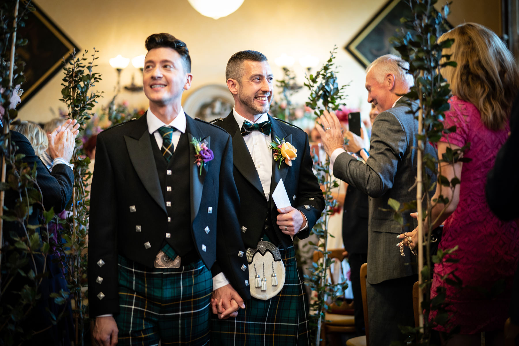 Newlyweds in kilts leave the Oak room at The Elvetham Hotel