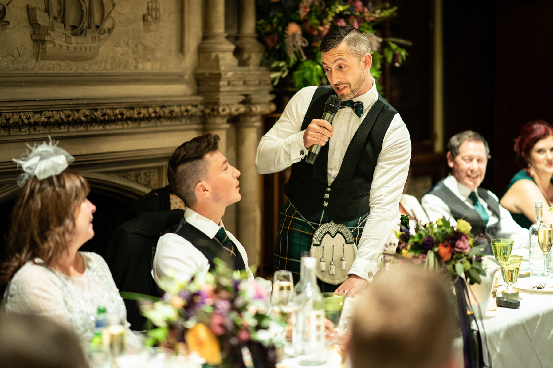 Groom looks at his new husband during the wedding speeches in the library at The Elvetham