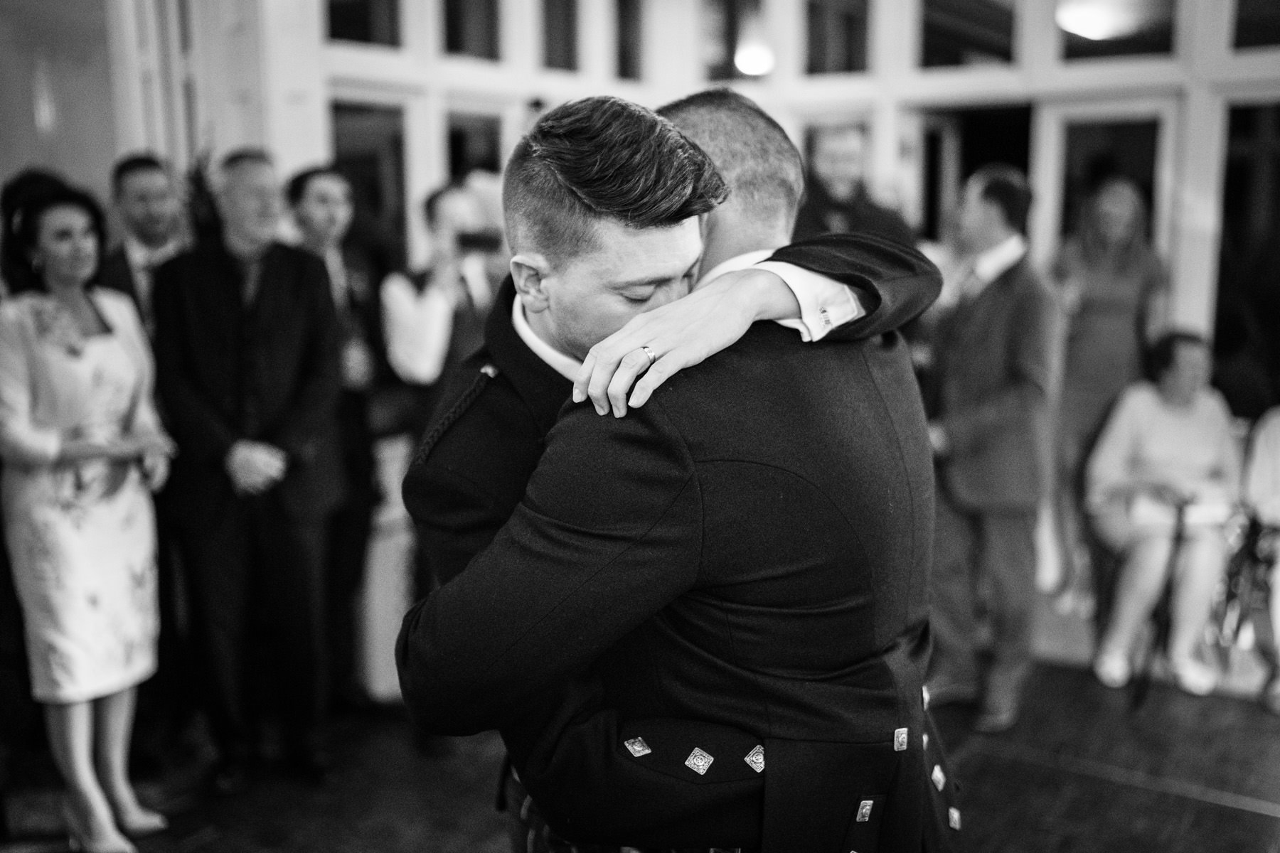 Two Grooms embrace during their first dance in the Winter Conservatory at The Elvetham