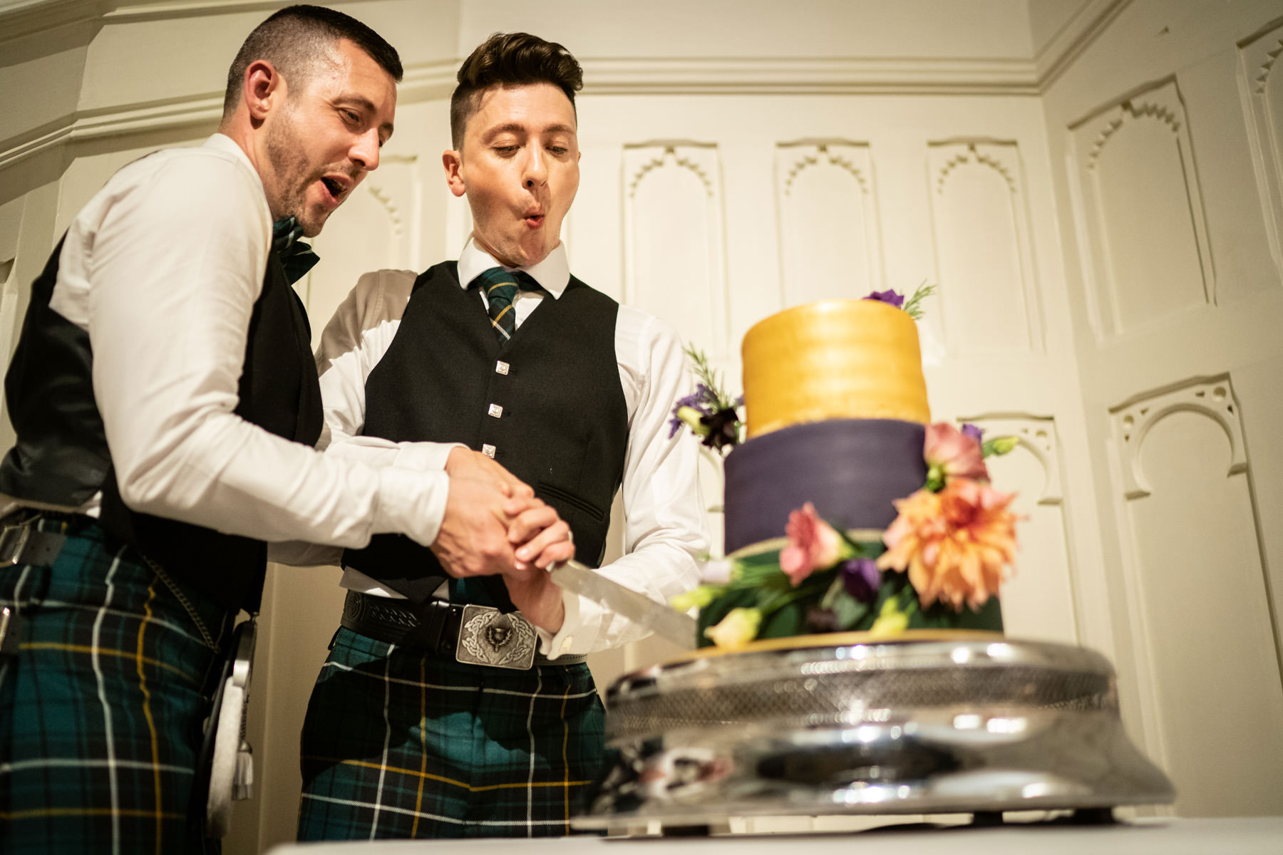 Two grooms cut their wedding cake