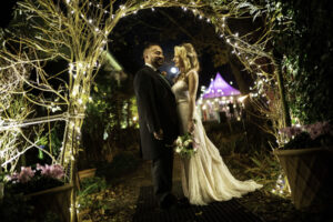 Bride and Groom pose beneath Floral Arch with fairy lights
