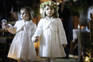 Flower girls hold hands in church