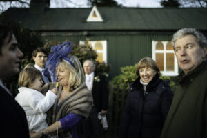 Flower girl feeds mother of groom a lollipop at Oxfordshire Wedding