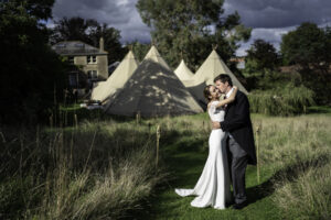 Bride and Groom embrace behind their wedding marquee in Dorset