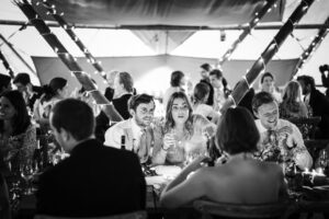 Guests chat during wedding breakfast in wedding Marquee